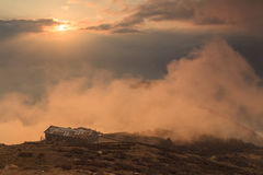Old house on top of a mountain in the clouds Stock Photo