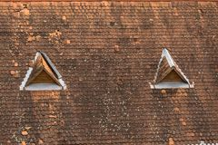 Old house top with traditional roof and little. Old house top with traditional roof and two triangle little windows Stock Images