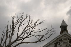 Old house and tree. Old house and the bare branches of a tree against a cloudy sky royalty free stock images