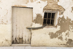 Old house wall with white door and window Stock Photos