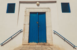 Old house white wall with blue door Royalty Free Stock Images