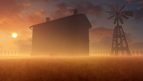 Old House And Windmill In Misty Sunset Stock Photo