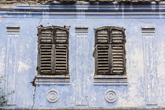 Old house windows. Two classic jalousie windows in old house wall Royalty Free Stock Images