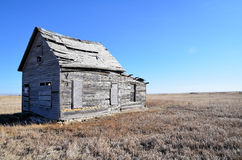 Old house on winter prairie. Boarded up weathered wooden house on a prairie with brown winter grass Royalty Free Stock Photo