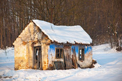 Old house in winter scenery. Abandoned and ruined old house in snow by the forest during winter season Stock Images