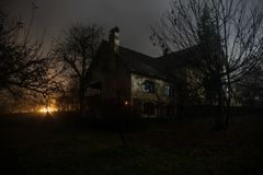 Free Old House With A Ghost In The Forest At Night Or Abandoned Haunted Horror House In Fog. Old Mystic Building In Dead Tree Forest. Royalty Free Stock Photography - 142798767