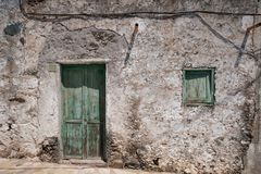 Old house with wooden door and weathered facade in rural villag. E stock photography