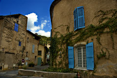 Old houses. A scene of a small street in rural France, flanked by old houses overgrown with creepers Royalty Free Stock Images