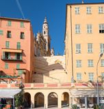 Old houses and the baroque basilica on the hill of Saint-Michel-Archange in Menton, France Royalty Free Stock Image