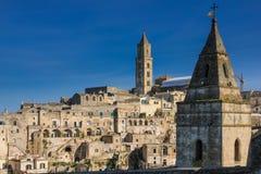 Old town. Matera. Basilicata. Apulia or Puglia. Italy. Old houses and bell tower of the Cathedral of Maria Santissima della Bruna and Church San Pietro Barisano stock image