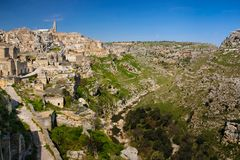 Old town. Matera. Basilicata. Apulia or Puglia. Italy. Old houses and bell tower of the Cathedral of Maria Santissima della Bruna and Gravina stream to the right stock images