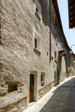 Old houses on bending street in medieval village of Bard, Italy. Old houses on antique road bending in medieval mountain village, shot on a bright summer day at Stock Image