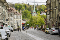 Old houses on a cobbled street in Bern. Bern, Switzerland - April 17, 2017: Old houses on a cobbled street in the old town. There are cars parked alongside the Stock Photo