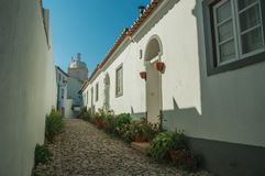Old houses in cobblestone alley on slope. Charming facade of old houses with whitewashed wall in cobblestone alley on slope, in a sunny day at Marvao. An amazing stock photo