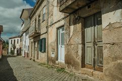 Old houses with cracked plaster wall and wooden door. Facade of old houses with cracked plaster wall and wooden door, in a deserted alley at Unhais da Serra. A stock photography