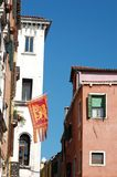 Old houses and  flag with Saint Mark lion Royalty Free Stock Photography