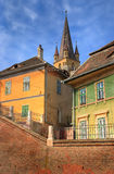 Old houses in front of a church. Old Transylvanian houses in front of a church tower in Sibiu, Romania, the European Cultural capital city in 2007 Royalty Free Stock Photography