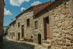 Old houses made of stone on cobblestone alley. Charming terraced old houses made of stone on cobblestone alley, in a sunny day at Linhares da Beira. A medieval stock photography