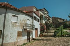Old houses in small square on slope with steps. Old houses with worn plaster and garden in small square on slope with steps, in a sunny day at Belmonte. A cute stock image