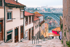 Old houses and stairs in Ribeira, Porto, Portugal. Traditional old houses in Ribeira and stairs down to the river Douro, Dom Luis I or Luiz I iron bridge on the stock images