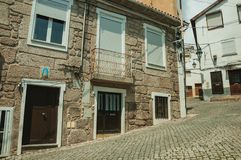 Old houses with stone wall in a deserted alley. Charming facade of old house with stone wall and wooden door in deserted alley, in a sunny day at Covilha. Known royalty free stock photos