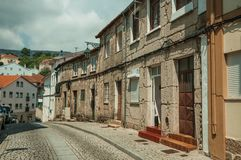 Old houses with stone wall in a deserted alley. Charming facade of old terraced houses with stone wall in deserted alley, in sunny day at Covilha. Known as the stock photo