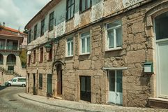 Old houses with stone wall in a deserted alley. Charming facade of old houses with stone wall and wooden door in deserted alley, in sunny day at Covilha. Known stock images