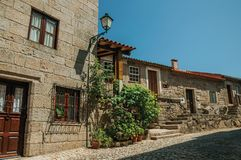 Old houses with stone wall and flowered bushes. Charming facade of old houses with stone wall and flowered bushes on deserted alley, in a sunny day at Monsanto royalty free stock photography