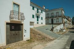 Old houses on street and deserted alley coming out on slope. Facade of old houses on street with wooden door and deserted alley coming out on slope at Castelo de stock photo