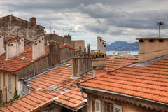Old houses with tiled roof in Cannes, Fran. Old houses with tiled roof and dramatic cloudy sky. Cannes, France before festival during springtime Stock Image