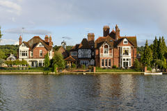 Old houses and a white canoe over river Thames, Marlow Stock Image