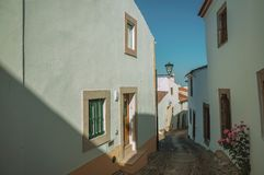 Old houses with whitewashed wall in an alley of Marvao. Charming facade of old houses with whitewashed wall in cobblestone alley on slope, in a sunny day at royalty free stock photography