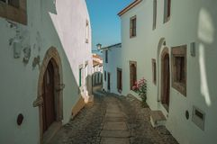 Old houses with whitewashed wall in an alley of Marvao. Charming facade of old houses with worn plaster wall and cobblestone alley on slope, in a sunny day at stock images