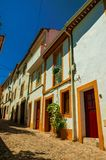 Old houses with whitewashed wall in alley on slope. Facade of old colorful houses with wall in alley on slope, on sunny day at Castelo de Vide. Nice little town stock photos