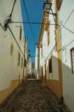 Old houses with whitewashed wall in alley on slope. Facade of old colorful houses with whitewashed wall in alley on slope, on a sunny day at Castelo de Vide royalty free stock images