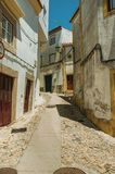 Old houses with whitewashed wall in cobblestone alley. Facade of old colorful houses with worn whitewashed wall in cobblestone alley on slope at Castelo de Vide stock images