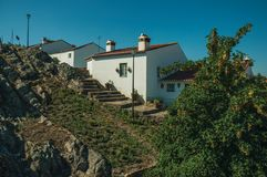 Old houses with whitewashed wall over rocks in Marvao. Old houses with whitewashed wall over rocky ridge, with stairs and leafy trees in a sunny day at Marvao stock images