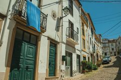 Old houses with worn plaster in alley on slope. Old terraced houses with worn plaster and wooden door in alley on slope, on sunny day at Castelo de Vide. Nice stock photos