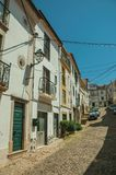 Old houses with worn plaster in alley on slope. Old terraced houses with worn plaster and wooden door in alley on slope, on sunny day at Castelo de Vide. Nice stock images