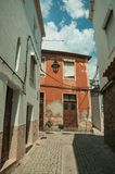 Old houses with worn plaster in a deserted alley on slope. Facade of old houses with worn plaster in a narrow deserted alley on slope, in a sunny day at Covilha royalty free stock photo