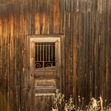 Old hovel. Wooden door with a lattice. Royalty Free Stock Images