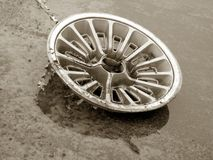 An old hubcap. Laying on wet pavement, sepia tones Royalty Free Stock Image