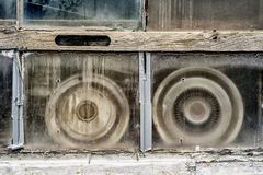 Old hubcaps in a dirty window. Vintage hubcaps house in Laval, Quebec royalty free stock photo