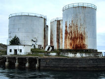 Old huge rusty oil tanks. Old industrial buildings left abandoned Royalty Free Stock Photo