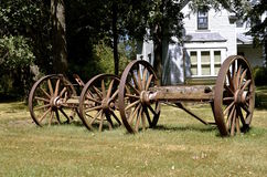 Old huge wagon wheels parked in front of a a farmhouse Royalty Free Stock Images