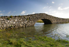 Old Hump Back Bridge, Aberffraw, Anglesey. Eighteenth Century stone hump back bridge, with water channel and blue sky. Aberffraw, Anglesey, Wales, United Stock Image