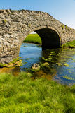 Old Hump Back Bridge, Aberffraw, Anglesey. Eighteenth Century stone hump back bridge, with water channel, the river Ffraw, and blue sky. Aberffraw, Anglesey Royalty Free Stock Photo