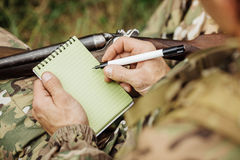 Old hunter loading his gun ans taking notes. Hunter loading his gun ans taking notes royalty free stock photography