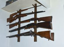 Old hunting guns hang on the wall. Old French hunting guns hang on the wall Stock Photo