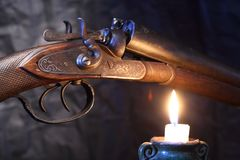 Old Hunting Shotgun. Ancient hunting shotgun closeup near lighting candle on dark background Stock Photography